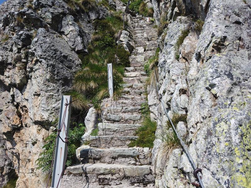Steep stairway carved out of stone on a mountain path. Steel cables on its sides. Orobie. Italian Alps stock photos