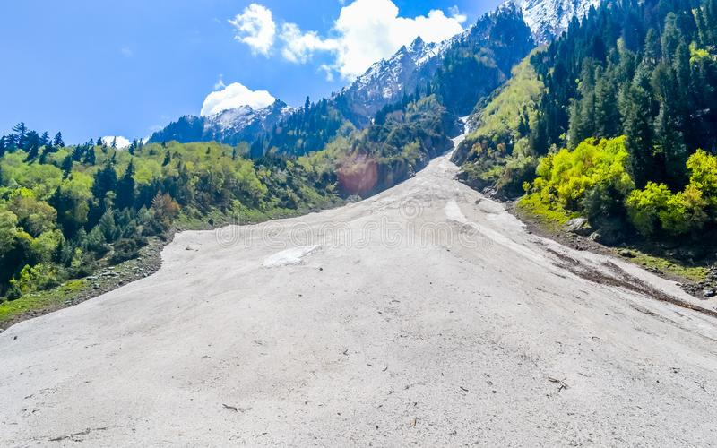 A steep V shaped fluvial valley formed by one of the headstreams of the flowing Ganges river water with steep gradients in. Himalayan mountain ranges royalty free stock photo
