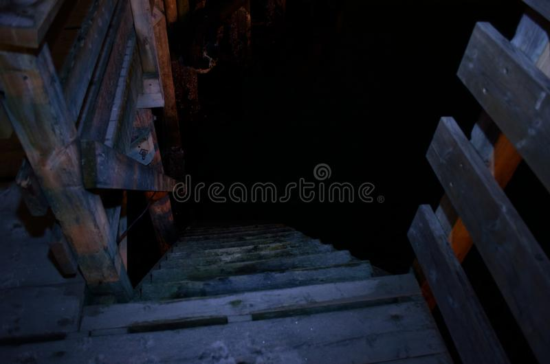 Steep wooden pier staircase leading down to sea level at night stock photos