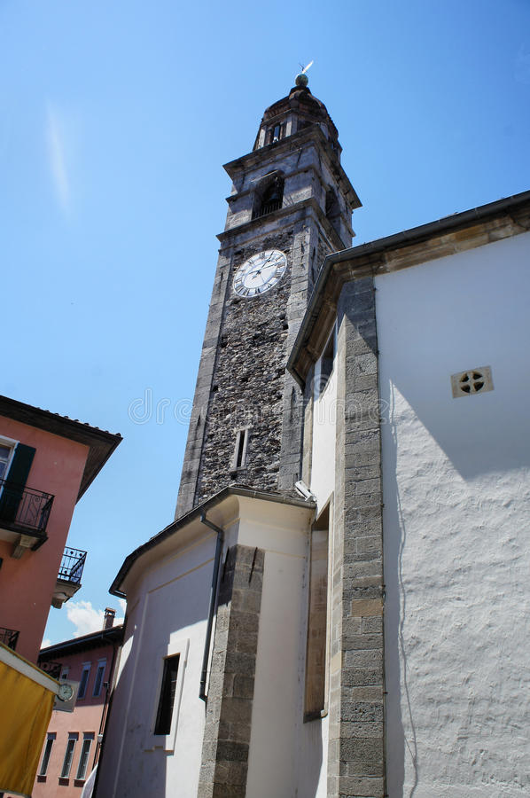 A steeple and narrow alleys. View from the frog perspective to a church tower, narrow streets in Ascona in Ticino, Switzerland royalty free stock photos