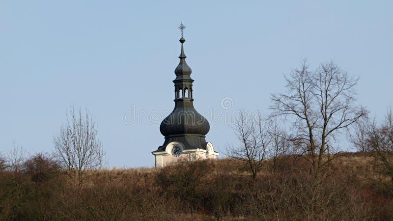 Steeple sopra una chiesa con i rami e gli alberi asciutti in primo piano immagini stock libere da diritti