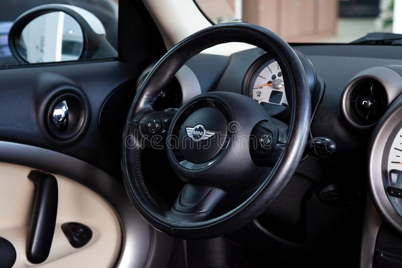 Steering wheel of chrome and leather details in the interior design of a luxurious black and beige car mini Cooper against the royalty free stock photos