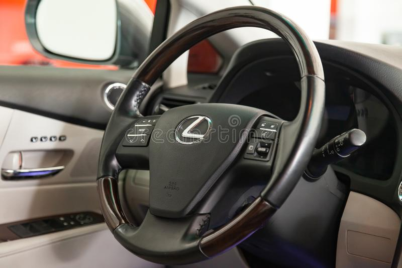 Steering wheel with parts of wood and chrome-plated details in the interior design of a luxurious black Lexus RX350 car against stock image