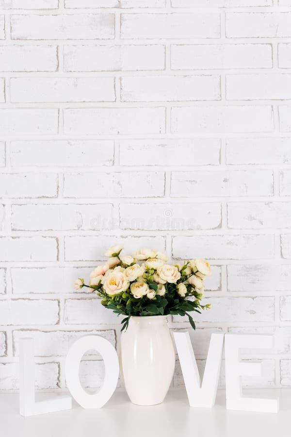 Steg blommor och träordförälskelse över den vita tegelstenväggen arkivbilder