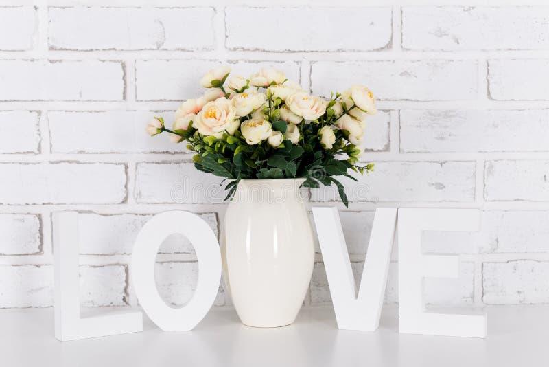 Steg blommor och vit träordförälskelse, över den vita tegelstenväggen royaltyfri fotografi