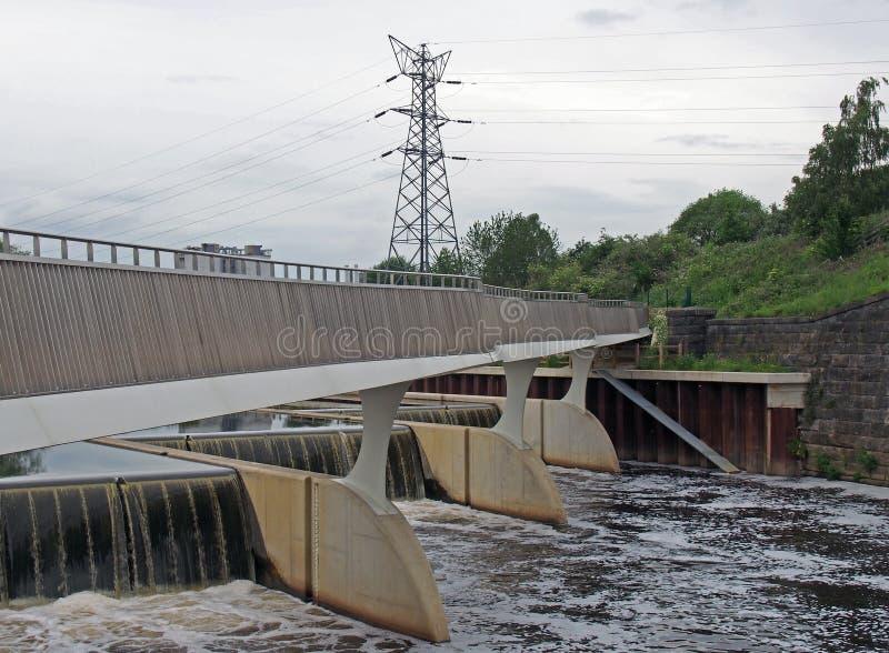 Steg, der das Fluterleichterungswehr auf dem Aire am knostrop Leeds mit Strommasten in einem ländlichen industriellen kreuzt lizenzfreies stockfoto