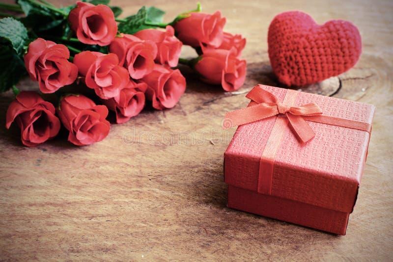 Steg med den röda gåvaasken och röd hjärtaform på trätabellen fotografering för bildbyråer