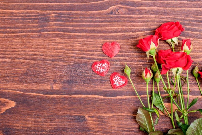Steg med röda kronblad med hjärtor för valentins dag på galten arkivfoton