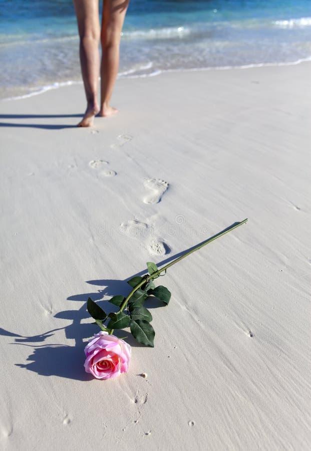 Steg på sand av stranden och och kvinnlig fot på en havskant royaltyfria bilder