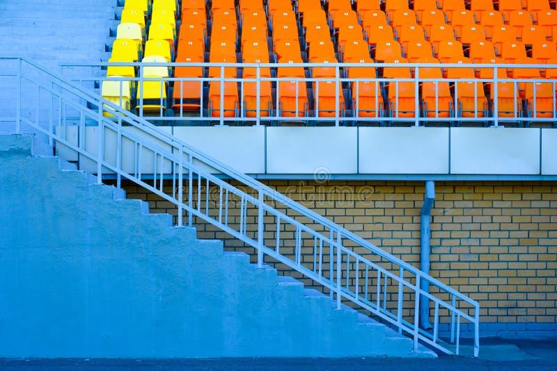 Stege- och sporttribun från gula och orange plast- platser arkivfoton