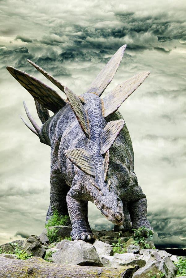 Stegosaurus που στέκεται στο βράχο με το δραματικό ουρανό στο υπόβαθρο στοκ φωτογραφίες