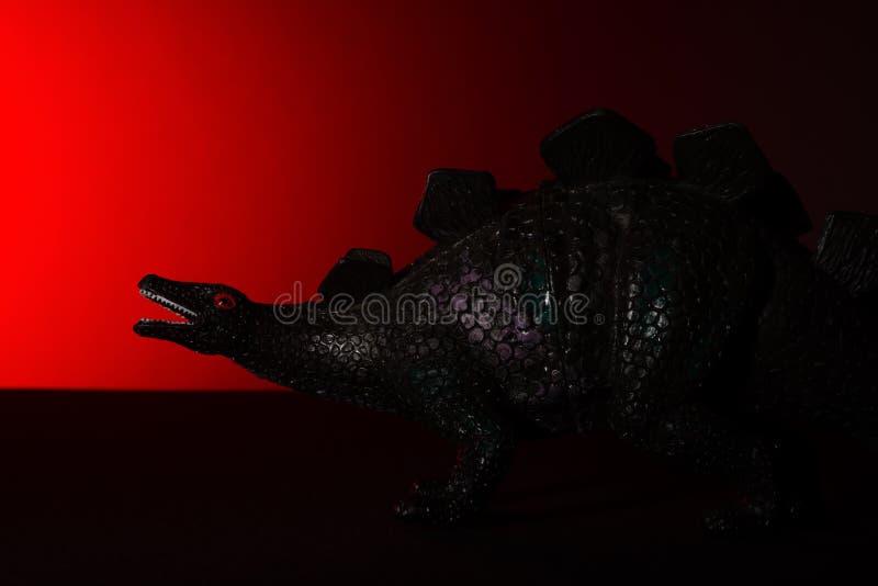 Stegosaurus com luz do ponto na luz principal e vermelha no fundo fotos de stock