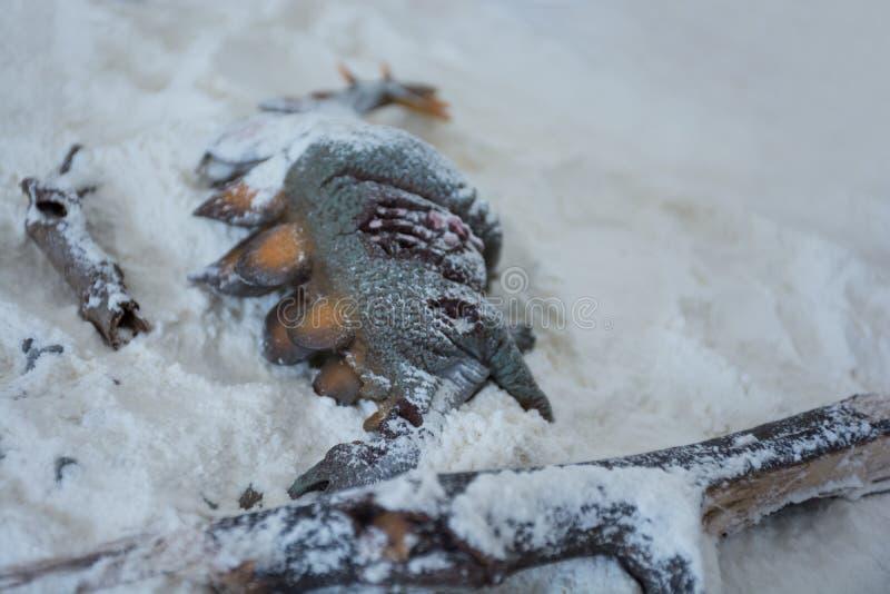 Stegosaurus inoperante sob a neve na terra do inverno foto de stock royalty free