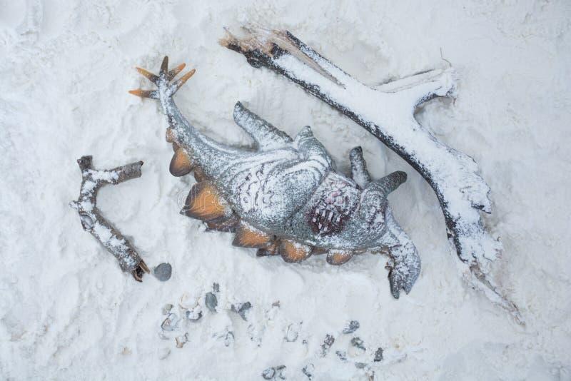 Stegosaurus inoperante sob a neve na terra do inverno foto de stock