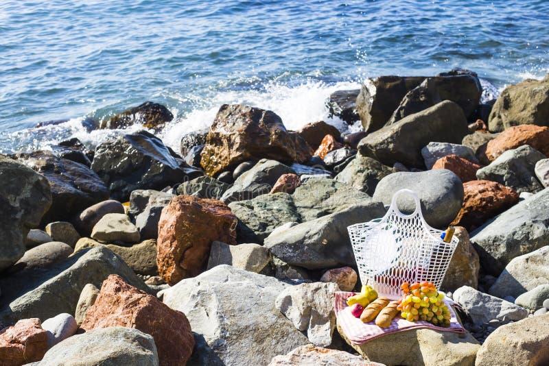 Stehen Sie durch das Meer mit Trauben, Äpfeln, Birnen, Stangenbroten, Wein und einem Korb auf der Bettdecke still stockbilder