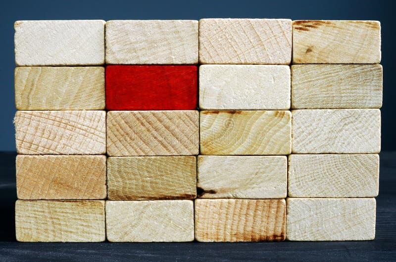Stehen Sie heraus vom Mengenkonzept Roter Holzklotz und Weiß lizenzfreie stockfotos