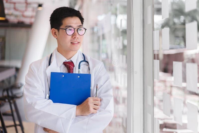 Stehende Arme asiatischen intelligenten Doktors gekreuzt stockbild