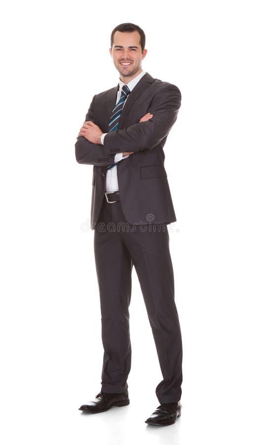 Stehende Arme des überzeugten jungen Geschäftsmannes gekreuzt lizenzfreies stockfoto