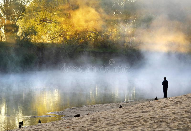 Stehende Gewissensprüfung des einsamen Mannes auf nebeligem nebelhaftem Fluss der Bank lizenzfreie stockfotografie