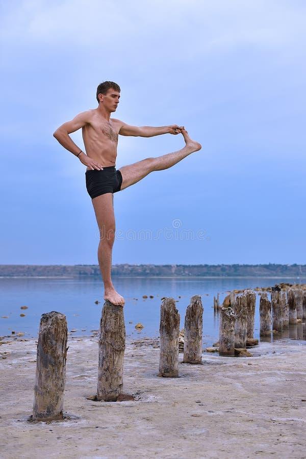 Stehende Yogahaltung des jungen Mannes stockfotos