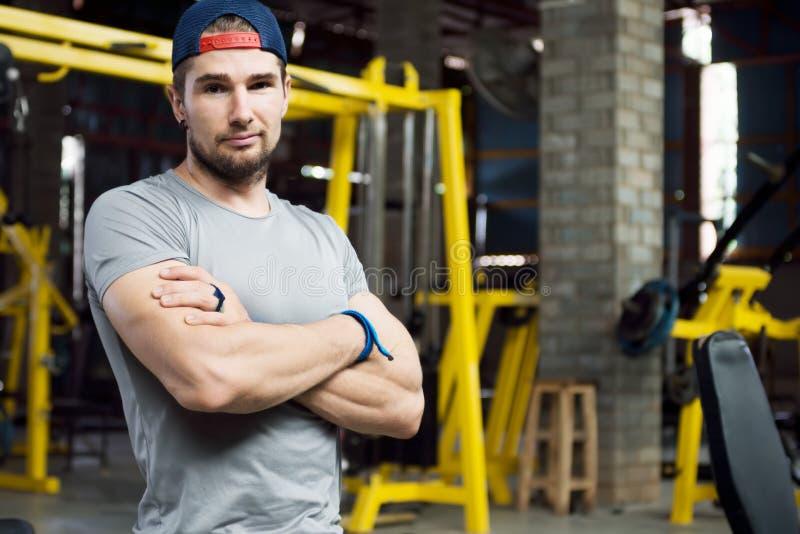 Stehender Arm des jungen muskulösen Trainers mit sarkastischem Blick lizenzfreie stockfotografie