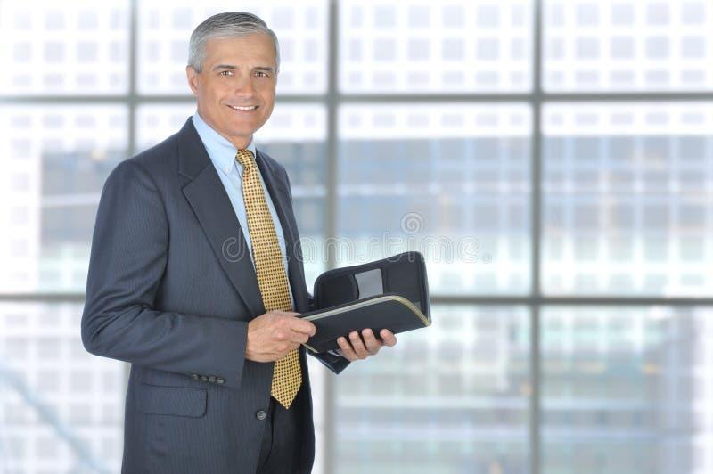 Stehender Geschäftsmann mit Planer-Notizbuch stockfotografie