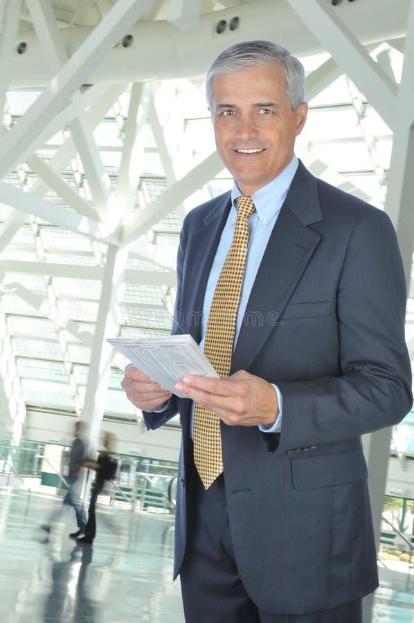 Stehender Geschäftsmann mit Zeitung in der Vorhalle lizenzfreie stockbilder