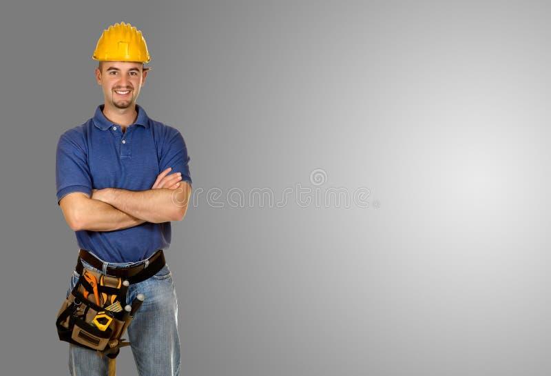 Stehender junger Grauhintergrund der manuellen Arbeitskraft stockbilder