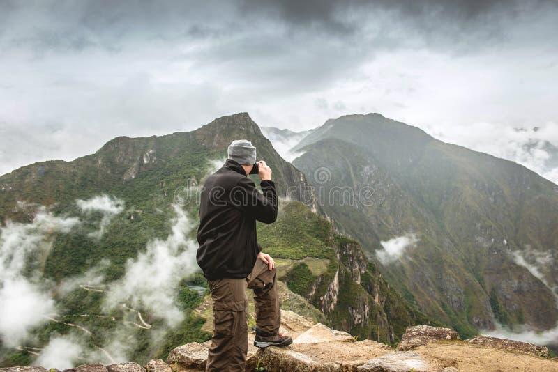 Stehender Mann, der Fotos von Machu Picchu macht stockfoto