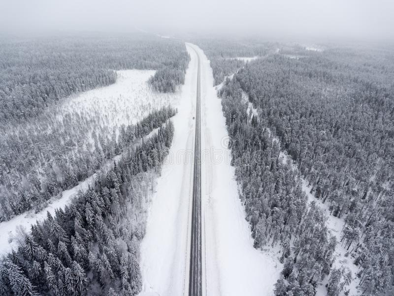 Stehender Straßenrand des kleinen einzelnen Autos in der winterlichen Straße am Blizzard, Vogelperspektive am geraden Nordweg Kar lizenzfreie stockfotos