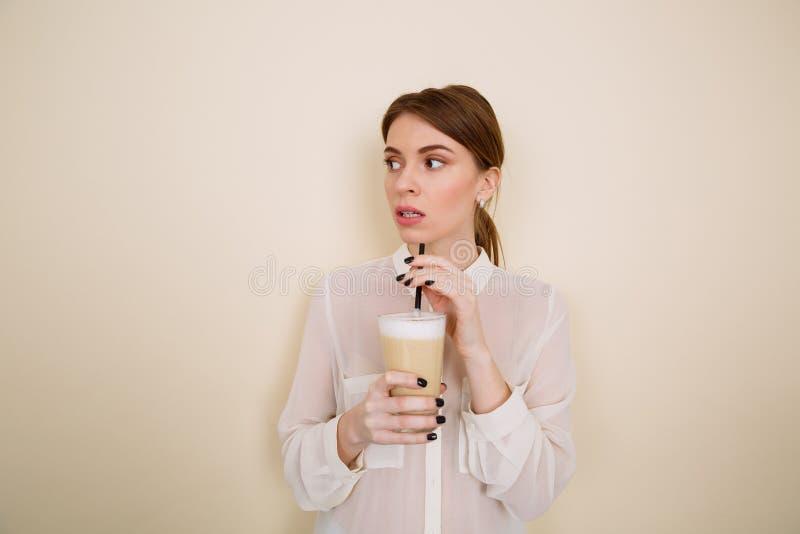 Stehender und trinkender Kaffee der nachdenklichen schönen jungen Frau mit Milch lizenzfreies stockbild