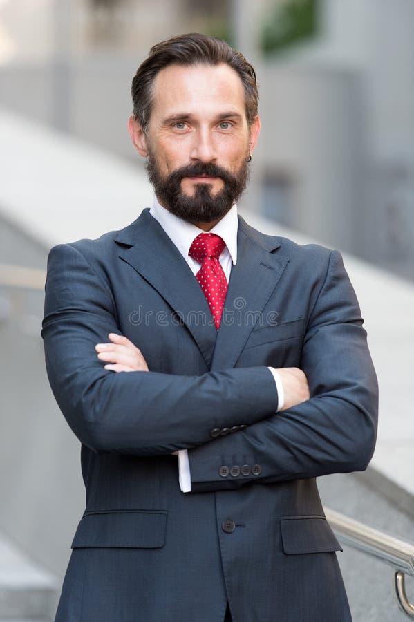 Stehendes äußeres Bürolächeln und -Händchenhalten des überzeugten angenehmen Geschäftsmannes gekreuzt Ich bin Berufs Porträt von  lizenzfreie stockfotografie