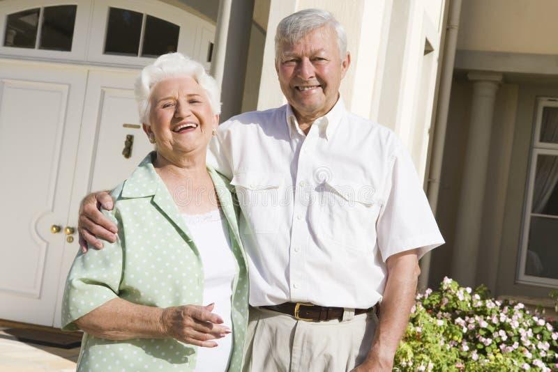 Stehendes äußeres Haus der älteren Paare lizenzfreie stockfotos