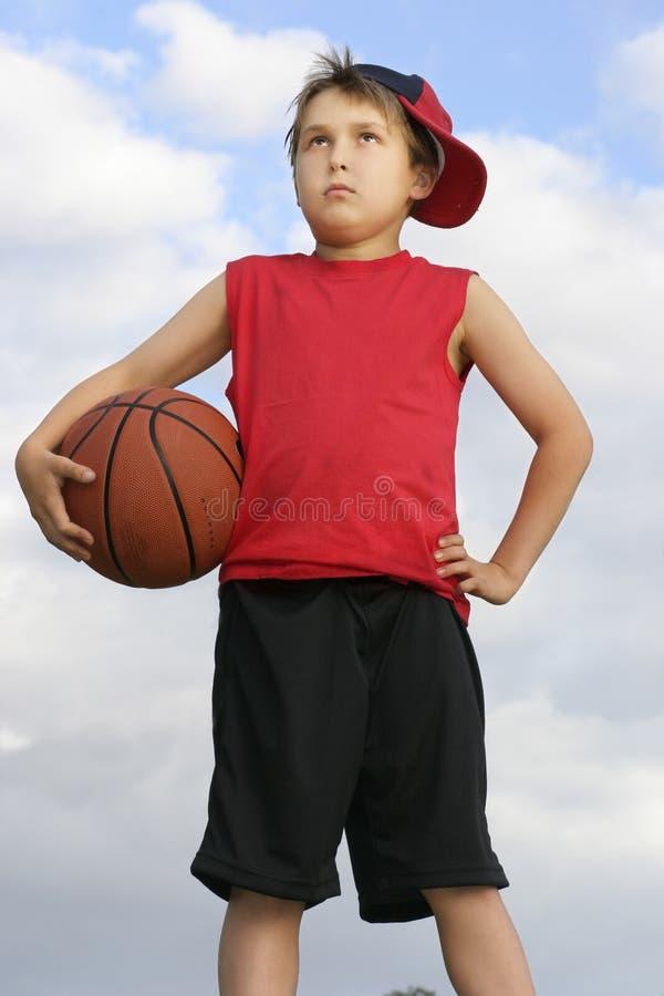 Stehendes Kind, das einen Basketball anhält stockfotos