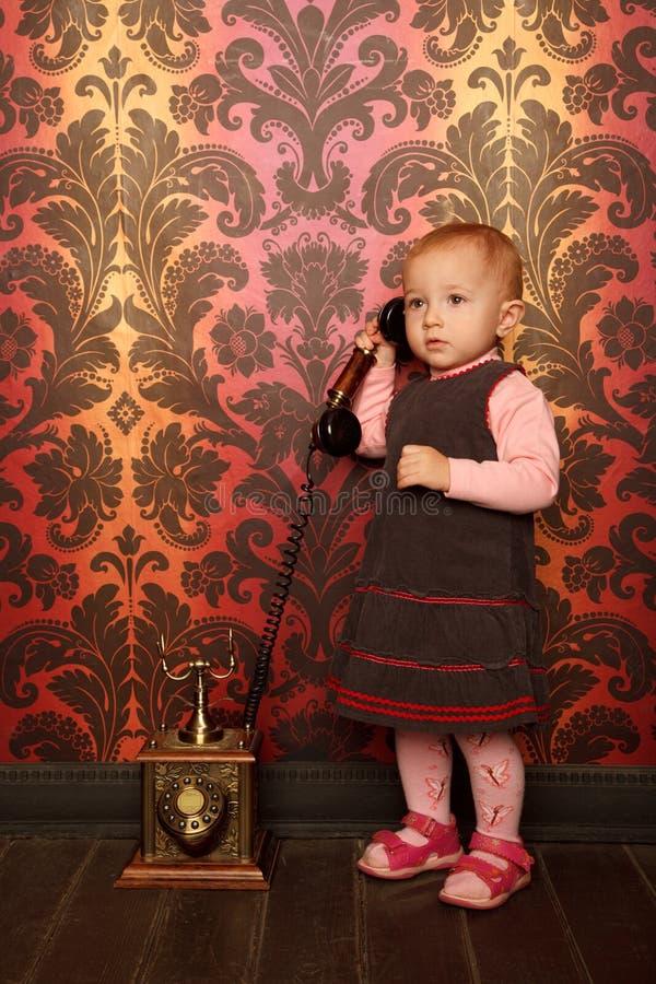 Stehendes kleines Mädchen, das am Retro- Telefon spricht stockfotografie