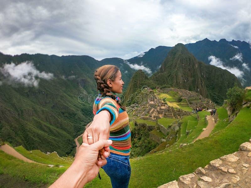 Stehendes Paarhändchenhalten, welches die Terrassen über Machu Picchu, der besuchte touristische Bestimmungsort in Peru erwägt stockbilder