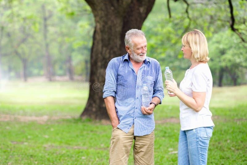 Stehendes Trinkwasser der älteren Paare lizenzfreie stockbilder
