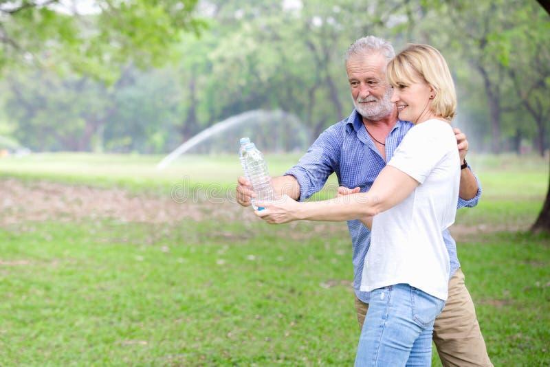 Stehendes Trinkwasser der älteren Paare lizenzfreie stockfotografie