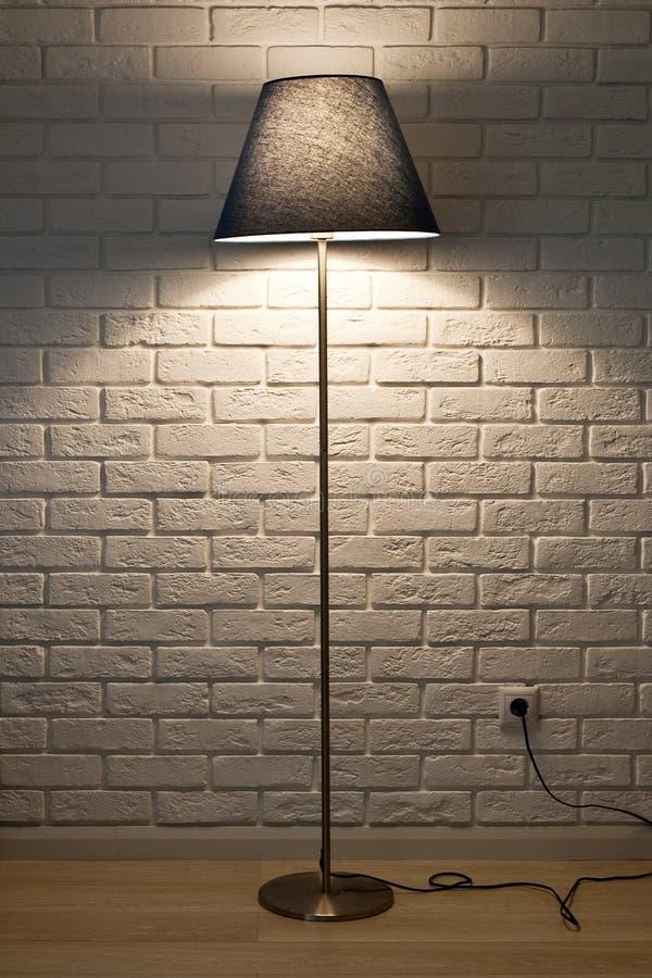 Stehlampe auf dem Hintergrund einer strukturierten Wand des weißen Ziegelsteines Hölzernes Regal Beschaffenheit, Hintergrund, Bel stockbilder