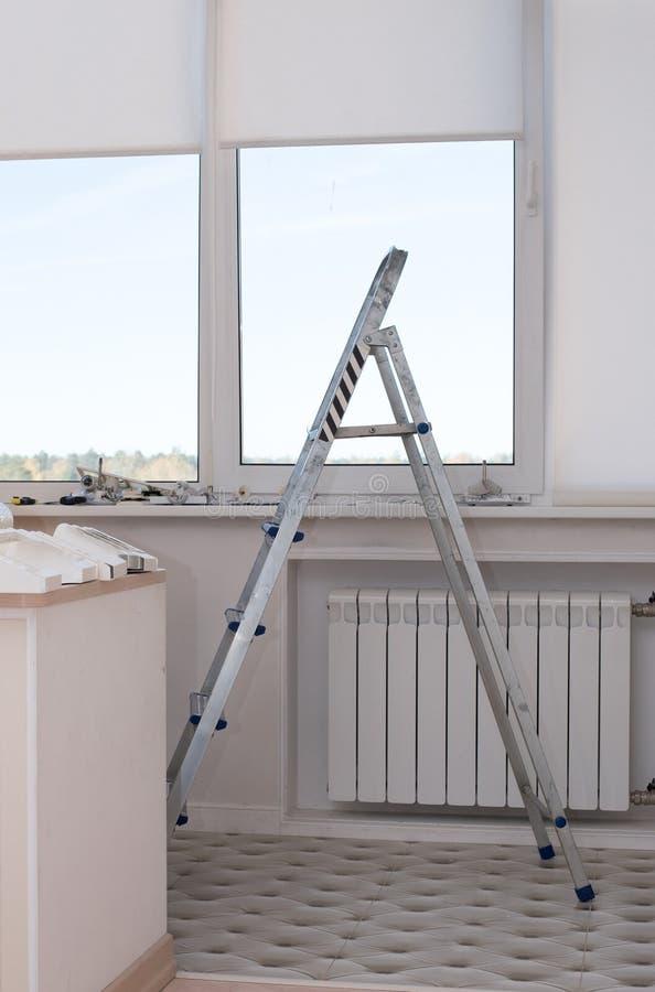 Stehleitertreppe in der Wohnung am Fenster vor dem hintergrund der Reparaturmaterialien lizenzfreie stockfotografie