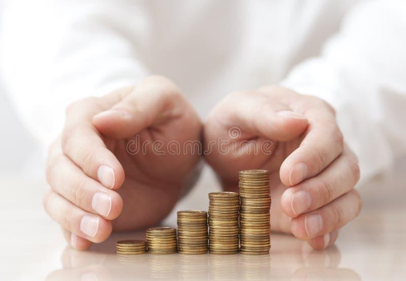 Steigende Münzen geschützt unter man& x27; s-Hände lizenzfreie stockfotografie