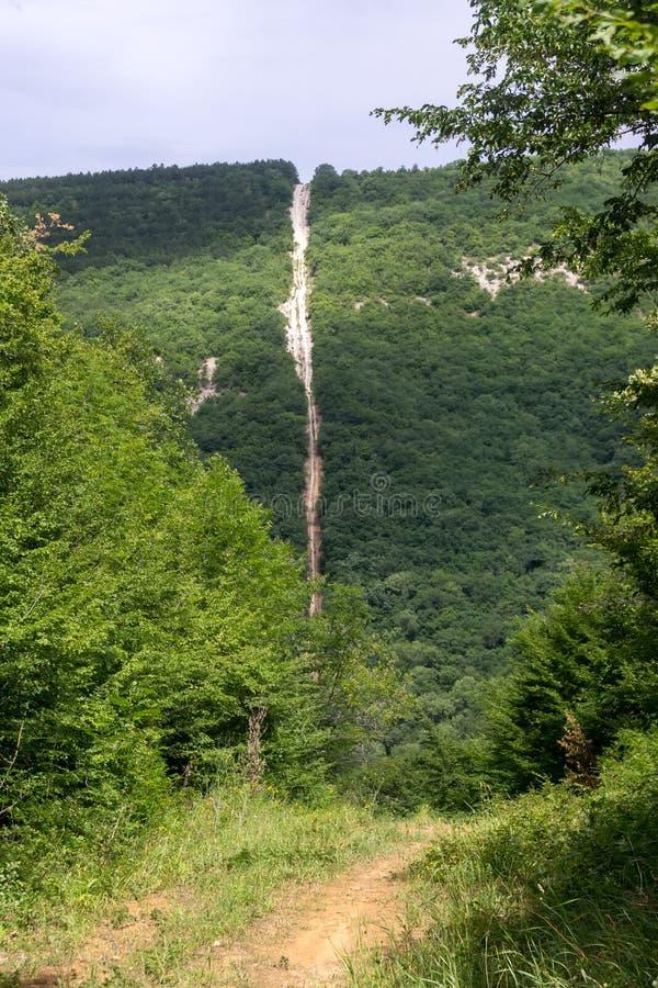 Steile afdaling van een beboste heuvel royalty-vrije stock afbeelding
