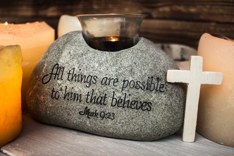 Stein mit christlicher Schrift mit hellem Kerzenkreuz stockbild