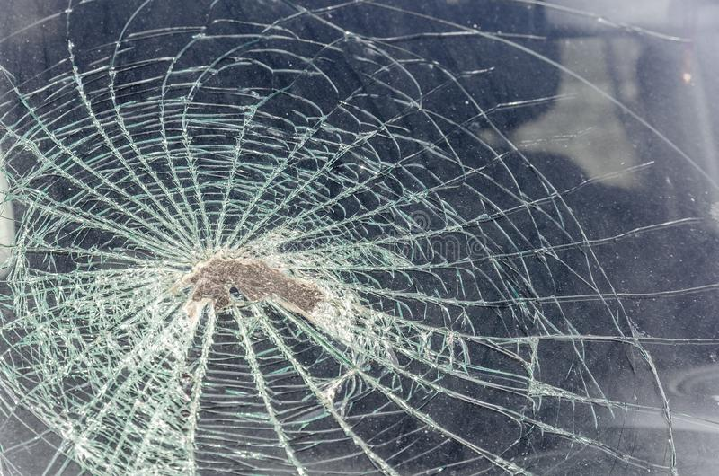 Stein oder ein Kopfstein zertrümmerten die Windschutzscheibe, während sie in das Auto mit Geschwindigkeit flog Fragmente und Spur lizenzfreies stockbild