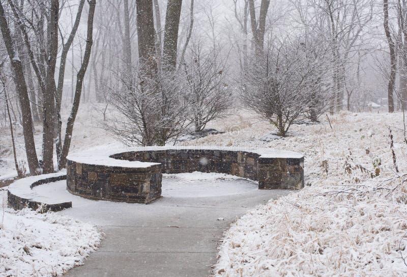 Steinbank in einem Park am Winter stockfotografie