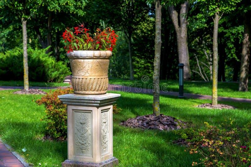 Steinblumentopf auf einem Steinsockel mit Blumen stockfotografie