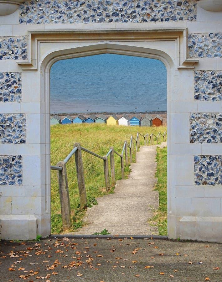 Steinbogenzugangs-Türeingang, zum von Küstenseeküsten-Schritthütten auf den Strand zu setzen stockfotografie