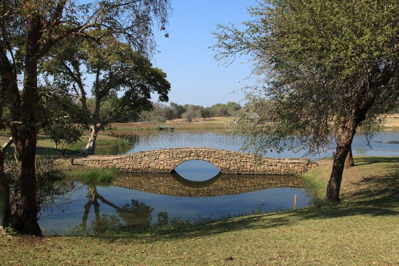 Steinbrücke über Fluss auf Golfplatz stockbilder