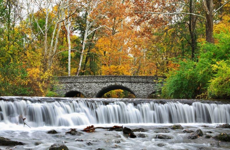 Steinbrücke und Wasserfall stockfotografie