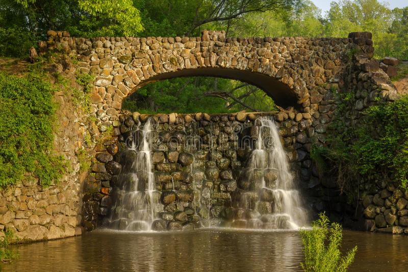 Steinbrücke und Wasserfall in Reynolda-Gärten stockfotos